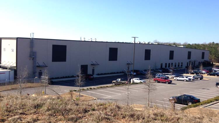 Projects: Large white building with six large black squares and 55 and 54 painted on the building.