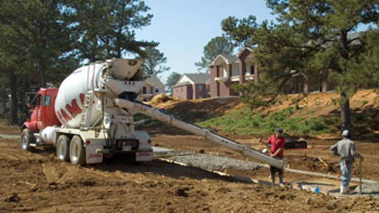 Projects: Concrete truck with two workers offloading concrete.