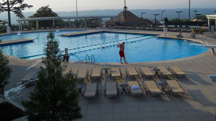 Projects: Large swimming pool with person cleaning the pool and multiple loungers