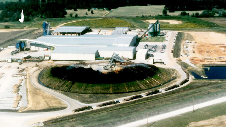 Projects: Aerial view of industrial building complex with 8 logging trucks in driveway